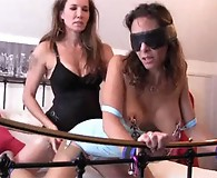 Jane clamps a horny sluts nipples before bending her over in the bed and hammering her from behind.