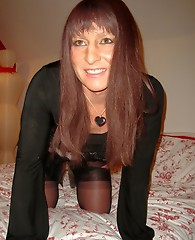 Sexy long haired crossdresser with great smile teasing in silky nylon stockings